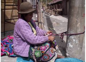 A hard-working weaver in the Pisac market, Peru.